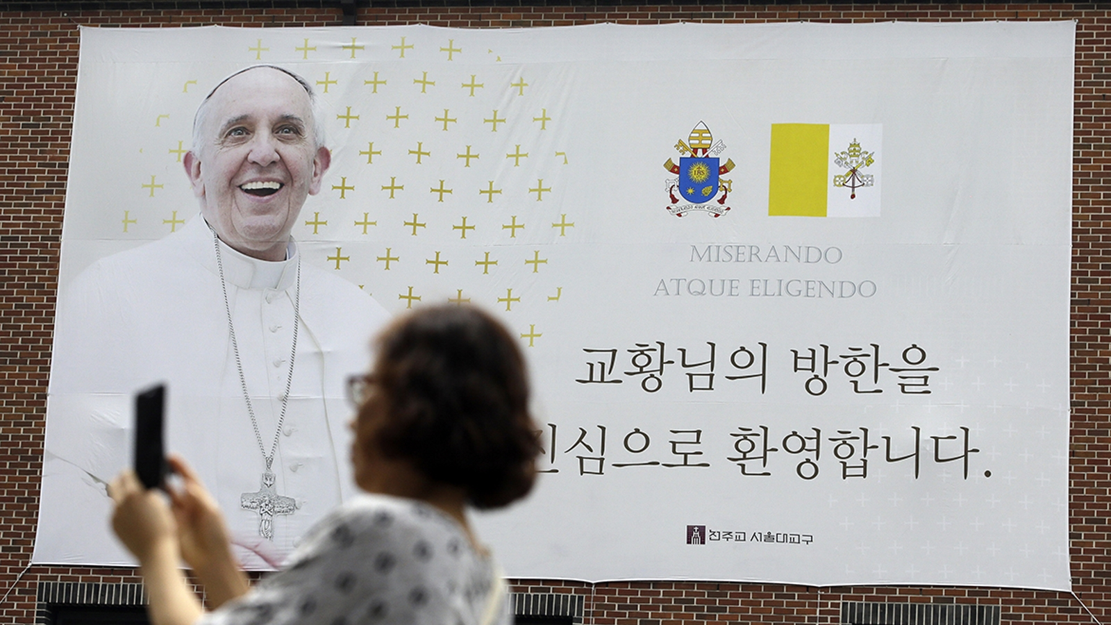 "A woman takes a photo near a welcome banner for Pope Francis at Myeong-dong Cathedral in Seoul, South Korea, Tuesday, Aug. 12, 2014. During his visit to the country this week, he'll bring a message of peace and reconciliation to the divided Korean peninsula and a call for young Catholics to take up the missionary charge themselves, spreading the faith on a continent where the Catholic Church is small but growing. The banner reads: ""We warmly welcome Pope's visit."" (AP Photo/Lee Jin-man)"