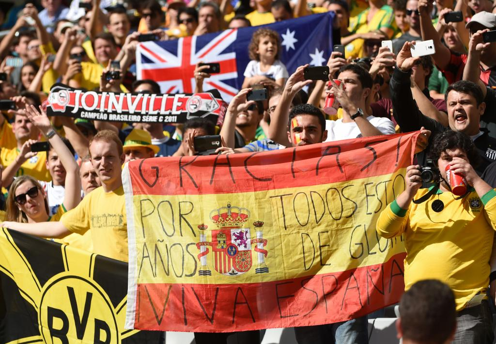 """Spanish fans hold a Spanish flag reading """"Thanks for all those years of glory"""" before a Group B football match between Australia and Spain at the Baixada Arena in Curitiba during the 2014 FIFA World Cup on June 23, 2014.  AFP PHOTO / WILLIAM WEST"""