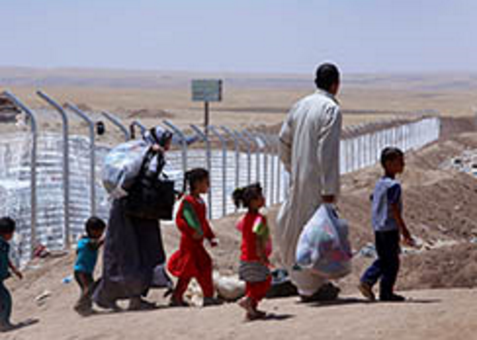 Members of an Iraqi displaced family, who fled violence in the northern city of Tal Afar, carry bags as they arrive at Khazer refugee camp near the Kurdish checkpoint of Aski kalak, 40 km West of Arbil, the capital of the autonomous Kurdish region of northern Iraq on July 27, 2014. Thousands of Christians and other minorities have fled the northern city of Mosul and other areas after a jihadist onslaught led by Islamic State insurgents swept swathes of Iraq's north and west the month before.  AFP PHOTO / SAFIN HAMED
