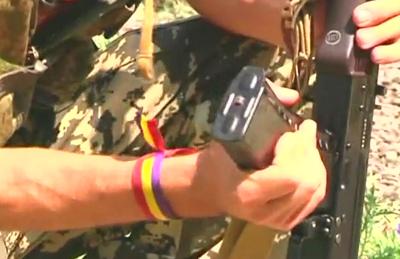 Uno de los tres ciudadanos español ,con su pulsera republicana, preparando su arma de fuego para el combate.
