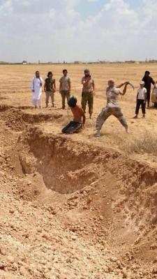 Islamista del SIL (ISIS, EIIL) unos segundos antes de cortar la cabeza de un cristianos de rodilla cerca de la fosa comuna