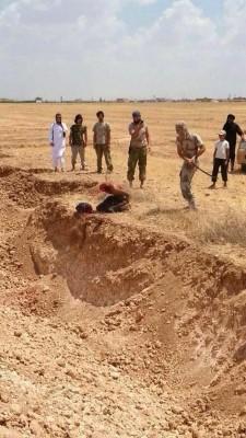 Islamista del SIL corta la cabeza del cristiano frente la fosa comuna.